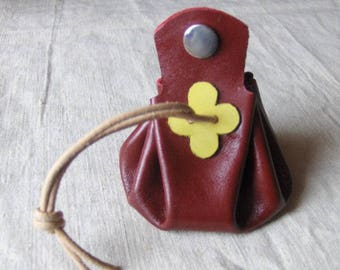 Coin purse is red leather with yellow clover