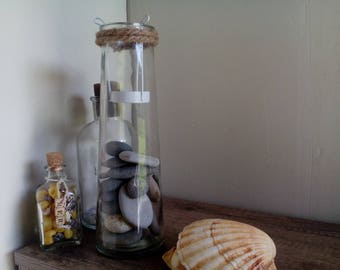 Candle holder, candle, glass flask and pebbles