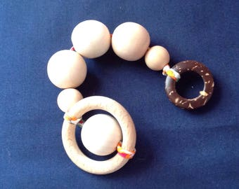 Wooden rattle and teether in her pouch.