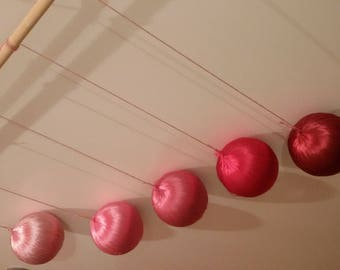 Pink Gobbi mobile made of real silk yarn from the Montessori