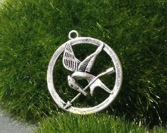 Hollow circular pendant, bird and arrow