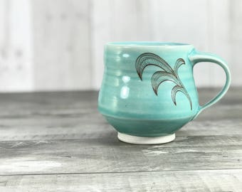 Aquamarine pottery mug. Porcelain pottery mug with flourishes. Handmade pottery mug. Turquoise pottery mug with hand drawn details.