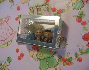 tiny kokeshi dolls in a glass shadow box
