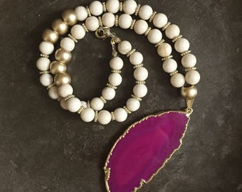 Hot pink geode slice pendant on cream color beaded necklace with gold accents