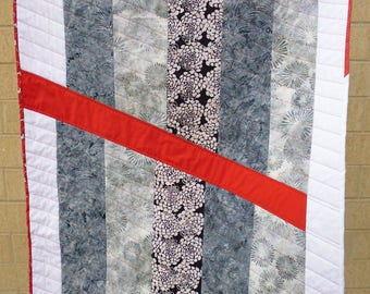 Gray and white crib or lap quilt, with a slash of red