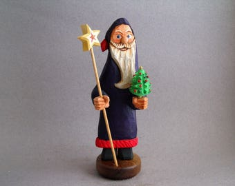 Carved Santa with walking staff and tiny Christmas tree