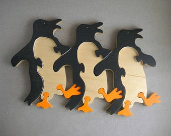 Wood jigsaw puzzle with three dancing penguins