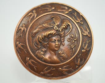One piece Brass Button with a head of a woman wearing a wide brimmed hat trimmed with Ostrich plumes fashionable at the turn of the century