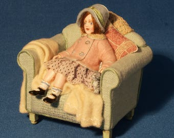 12th scale model of a child and kitten in an armchair