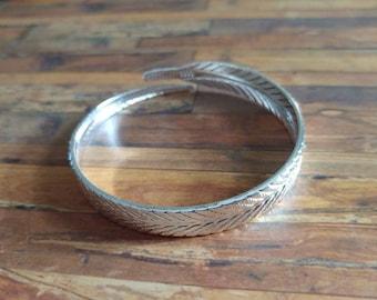 Silvertone feather bangle bracelet
