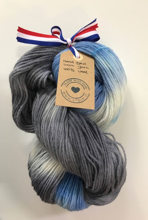 Hand dyed wool sock yarn in dark blue, grey and white.
