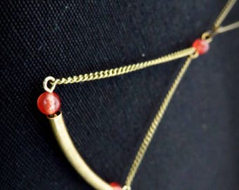 Graphic necklace tube curved brass and Red bead