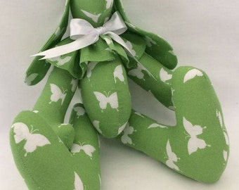 White butterflies on green fabric stuffed bunny