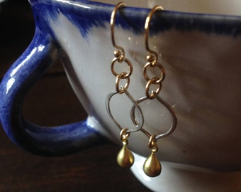 Dainty sterling silver lotus leaf earring with a golden dew drop.