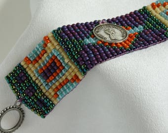 Loom Beaded bracelet with coin decoration in purple, orange, blue, white and iridescent green glass seed beads .