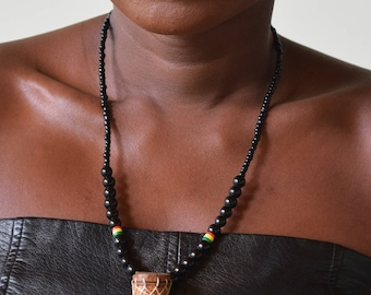 Beaded necklace with carved wooden drum pendant