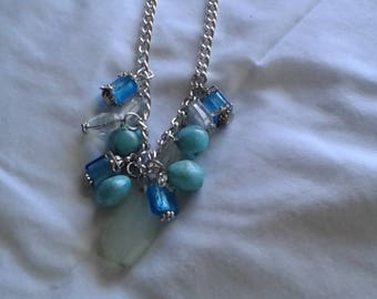 Beautiful shades of blue and green glass  bead on silver chain.