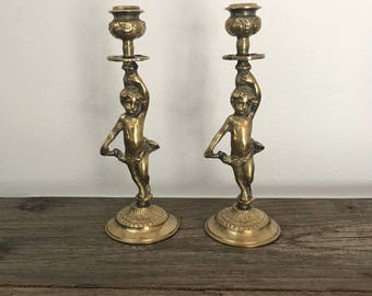 A pair of vintage brass angel cherub candlestick holders