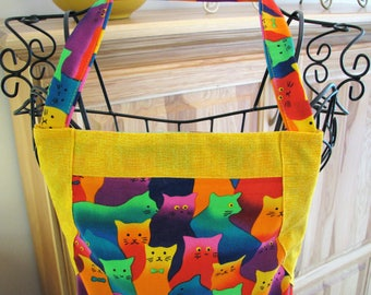 7605 Women's full apron with pocket and adjustable drawstring. 100% cotton. Colorful cats print with rickrack trim.