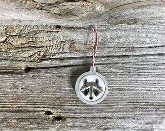 Modern raccoon Christmas tree ornament, cross stitch in silver wood laser cut frame by Canadian Stitchery