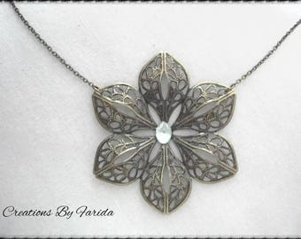 Necklace with pendant bronze filigree flower and a pale green rhinestones