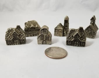 A Set of 6 Miniature Pewter Village with Church and Houses.