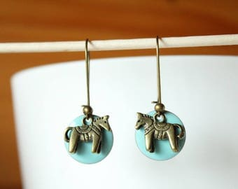 bronze earring with blue sequin and horse show