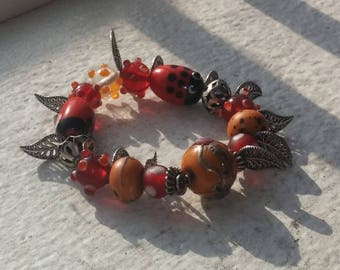 Cute bead bracelet with red and orange tones and leaf charms