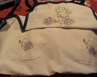 apron made of thick ecru fabric with a blue bias with embroidered grapes