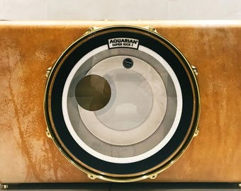 Limited edition CaseBass suitcase bassdrum in rawhide finish with brass hardware, gold kickport and maple shell