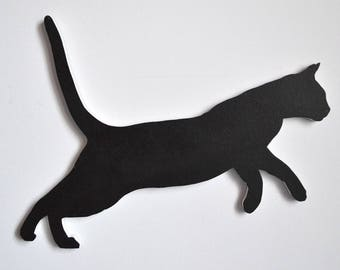Wall hanging of a cat leaping black and grey