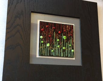 Framed fused glass piece, grey matted with red and green glass on black glass.