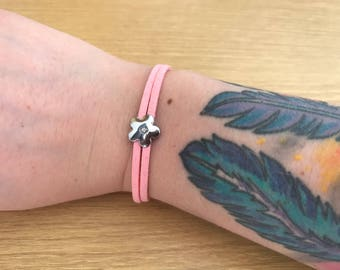 Pink faux suede bracelet with flower charm