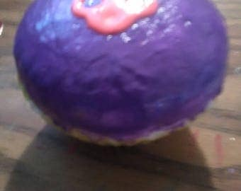 Yellow cake with purple frosting and a pink flower cupcake squishy