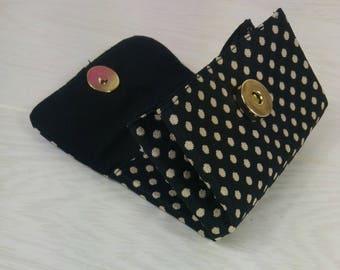 Black coin purse has gold dot