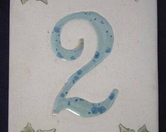 Number front door, crystallized blue '2' figure on a beige background, Ivy leaf decoration