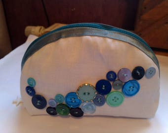 Small clutch makeup adorned with decorative buttons
