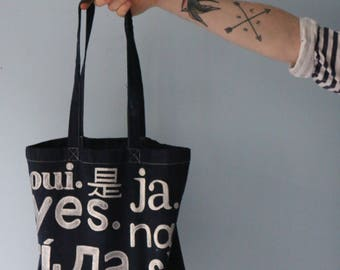 Handpainted typography tote bag. Yes, oui, ja, sí, sì, etc. Silver on navy