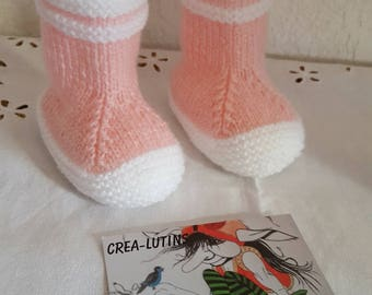 In white and pink size 0 to 3 months hand knitted baby boots.