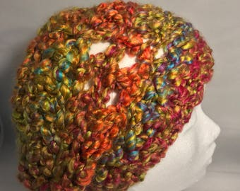 Ultimately slouchy super soft handcrafted crochet hat in Reds greens orange blue.