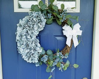 Luxurious spring or summer wreath with blue silk hydrangeas and small blue blossoms. Green artificial foliage and a ruffled white bow. Gift!