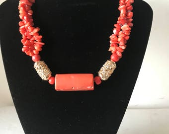 broken coral beaded necklace with two gold balls and a cylndrical one piece of coral bead at the centre.