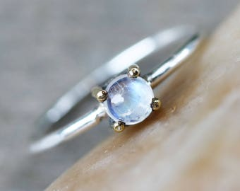 Dainty round moonstone ring with sterling silver bezel and brass prong setting