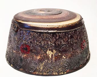 lidded jar with stamped patterns and decals