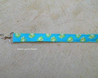Frog lanyard, Happy green frogs on turquoise blue fabric.