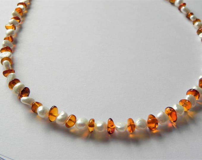 Baltic cognac amber and white freshwater cultured pearl necklace.