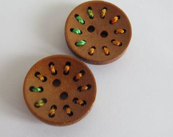 Round wood button with orange and green thread