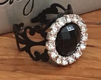 Black rhinestone ring. Black filigree band. One size fits all. Adjustable band.