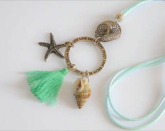 Long necklace featuring a shell, tassel, yellow/green starfish