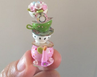 Miniature teapot with cups above